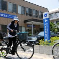 A cyclist rides by the public assistance section of the Edogawa Ward Office in Tokyo on Friday. | SATOKO KAWASAKI