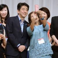 Prime Minister Shinzo Abe poses with panelists at the 19th International Conference for Women in Business on Sunday in Tokyo. | KYODO