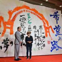 Artist Yoko Ono and Hiroshima Mayor Kazumi Matsui stand before a 4-meter-long, 6-meter-wide sheet with messages of peace written by local high school students in the city of Hiroshima on Wednesday, one week before the 69th anniversary of the atomic bombing. | KYODO