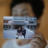 Kim Young-ja holds a photo of her brother, an abductee living in North Korea named Kim Young-nam (right), at her home in Jeonju, South Korea. The photo was taken during a reunion in 2006. | REUTERS