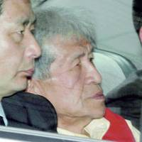Kunihiko Konishi (center), arrested on embezzlement charges, is taken to Osaka Prefectural Police headquarters on May 8. | KYODO PHOTO