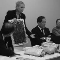 Black day: At a press conference at the Foreign Ministry, Fisher holds up a canvas covered in black scribbles she created in anger after hearing she had lost her appeal to the Supreme Court over her treatment by the Kanagawa police. | COURTESY OF CATHERINE FISHER