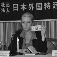Landmark win: At the Foreign Correspondents Club of Japan in November, Fisher holds up the symbolic amount of compensation she agreed to receive to settle her civil court case in Milwaukee against former U.S. serviceman Bloke Deans for the 2002 rape. | COURTESY OF CATHERINE FISHER