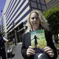 Uncomfortable truths: After writing a message to U.S. Ambassador to Japan Caroline Kennedy inside a copy of her book, Australian activist Catherine Fisher waits to present it to a member of staff at the U.S. Embassy in Tokyo on Friday. | DAMON COULTER