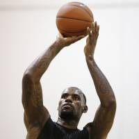 The world waits: LeBron James shoots a free throw at his Skills Academy in Las Vegas on Wednesday on the same day he met with Miami Heat president Pat Riley. | AP