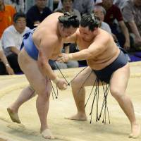 Strength for victory: Yokozuna Kakuryu shoves maegashira Tamawashi out of the raised ring on Thursday at the Nagoya Grand Sumo Tournament. | KYODO