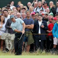 Six up: Rory McIlroy chips onto the green at the 17th hole during the third round of the British Open on Saturday. | AFP-JIJI