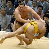 Easy does it: Hakuho takes down Shohozan on the second day of the Nagoya Grand Sumo Tournament on Monday. | KYODO