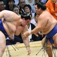 Timing is everything: Ozeki Kotoshogiku (right) takes control against Aoiyama on Tuesday at the Nagoya Grand Sumo Tournament.  | KYODO