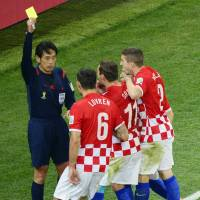 Somebody has to do it: Japanese referee Yuichi Nishimura is confronted by Croatian players during the opening game of the 2014 World Cup in Sao Paulo on June 12. | KYODO