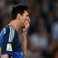 The agony of defeat: Argentina's Lionel Messi reacts after his team's loss to Germany on Sunday. Messi was later awarded the Golden Ball as the tournament's top player. | AFP-JIJI