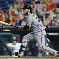 Time to go home: The Giants' Brandon Crawford hits a bases-clearing double in the 14th inning against the Phillies on Tuesday in Philadelphia. San Francisco won 9-6.   AP