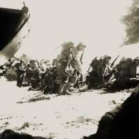 First wave: U.S. Marines take cover behind a sand dune on Saipan in the Mariana Islands while waiting for reinforcements in June 1944.  | SGT. JAMES BURNS. (U.S. MARINE CORPS)/AP