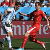 At odds: Argentina's Angel Di Maria (left) and Switzerland's Stephan Lichtsteiner compete on Tuesday.   AFP-JIJI