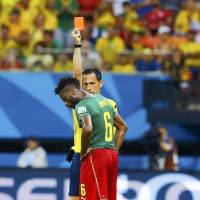 Looking into things: Cameroon's Alex Song is shown a red card after delivering an elbow to the back of Croatia's Mario Mandzukic (right) during their match on June 18.   KYODO