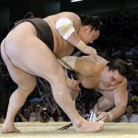 A skilled tactician at work: Hakuho sends rival yokozuna Harumafuji tumbling to the raised ring on Sunday at the Nagoya Grand Sumo Tournament.  | KYODO