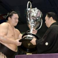 Familiar scene: Hakuho (left) on Sunday receives the Emperor's Cup for the 30th time in his illustrious career.  | KYODO