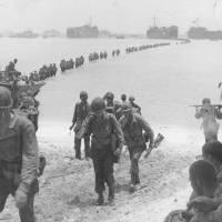 In the shallows: American reinforcements land on Saipan in June 1944.   KYODO