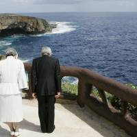 Silent tribute: The Emperor and Empress bow toward 'Suicide Cliff' in June 2005,  a rugged location where Japanese civilians committed suicide. | KYODO