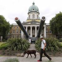 Double trouble: A man walks his dog past the newly re-opened Imperial War Museum in London on July 16. | REUTERS
