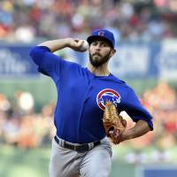 Four outs away: Chicago's Jake Arrieta throws a pitch against Boston in the first inning on Monday night. | REUTERS