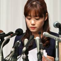 Digging deeper: Haruko Obokata, a researcher at Riken Research institution, checks her notes during a news conference in Osaka on April 9. | BLOOMBERG