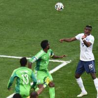 Ready to rise: France's Paul Pogba prepares to head in a goal against Nigeria in their second-round match on Monday in Brasilia. France won 2-0. | AFP-JIJI