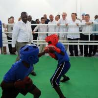 A place to train: United Nations Secretary-General Ban Ki-moon (center) and IOC president Thomas Bach (right of center) watch young boxers at the new facilities at the Sport for Hope Centre in Port-au- Prince, Haiti. | AFP-JIJI