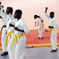 Dedication and fitness: A group of young martial arts students practice while authorities tour the new facilities that were inaugurated on Tuesday at the Sport for Hope Centre in Port-au-Prince. | AFP-JIJI