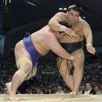 Last man standing: Kotoshogiku (left) shoves Takayasu out of the ring at the Nagoya Grand Sumo Tournament on Saturday. | KYODO