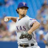 Back in action: The Rangers' Yu Darvish pitches against the Blue Jays on Friday in Toronto. Texas won 5-1. | AP