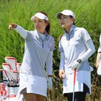 Second place is that way: Ai Miyazato (left) and Sakura Yokomine, playing for first-place Japan, speak to each other during the second round. | KYODO