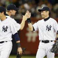 All in a day's work: Yankees oufielder Ichiro Suzuki high-fives a teammate after New York's win over Toronto on Friday at Yankee Stadium. | KYODO