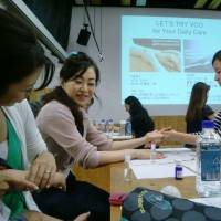 During an environmental event held on July at the Minato City Eco-Plaza, participants enjoy hand massages using coconut oil. | CHIHO IUCHI