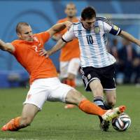 Tough to stop: Argentina's Lionel Messi tries to avoid a tackle by the Netherlands' Ron Vlaar in their World Cup semifinal on Wednesday night. | AP