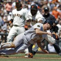 Two rundowns: San Francisco's Pablo Sandoval tags out Pittsburgh's Gaby Sanchez to complete a double play on Wednesday. | AP