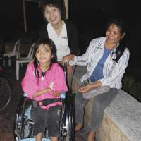 First set of wheels: Michiyo Yoshida (standing) delivers a used wheelchair to a child in Cebu, central Philippines, in January, so she can start going to school. | TAIZO YOSHIDA