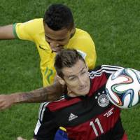 Germany's Miroslav Klose (bottom) and Brazil's Luiz Gustavo fight for the ball during the World Cup semifinal soccer match between Brazil and Germany at Mineirao Stadium in Belo Horizonte, Brazil, on Tuesday. Germany stunned Brazil to advance to the World Cup final in a 7-1 victory over the hosts. | AP