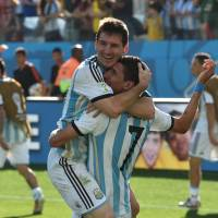 Feel the love: Argentina's Lionel Messi (left) hugs teammate Angel Di Maria during their match against Switzerland on Tuesday in Sao Paulo. Di Maria scored in extra time to give Argentina a 1-0 win. | AFP-JIJI