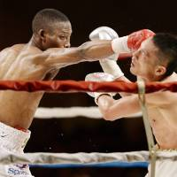 On target: South Africa's Zolani Tete punches Teiru Kinoshita during the seventh round of their IBF vacant super flyweight title bout on Friday in Kobe. Tete won by unanimous decision.   | KYODO