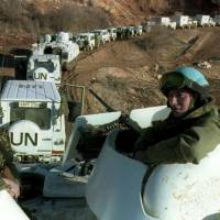 Two Dutch soldiers ride on an armored vehicle accompanying a Dutch-U.N. convoy of 56 engineering vehicles on their way to Lukavac in Bosnia-Hercegovina on Feb. 28, 1994. A court in the Netherlands ruled Tuesday that the Dutch state was responsible for the deaths of more than 300 victims of the Srebrenica massacre, the worst atrocity on European soil since World War II. | AFP