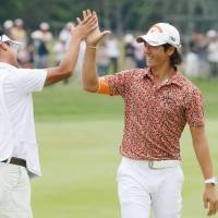 The wait is over: Ryo Ishikawa high-fives his caddie after winning the Shigeo Nagashima Invitational on Sunday in Chitose, Hokkaido. | KYODO