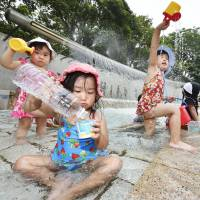 Children play with water in a fountain in Edogawa Ward, Tokyo, on Wednesday. Mercury hit the highest levels this summer in many areas of the nation. | KYODO