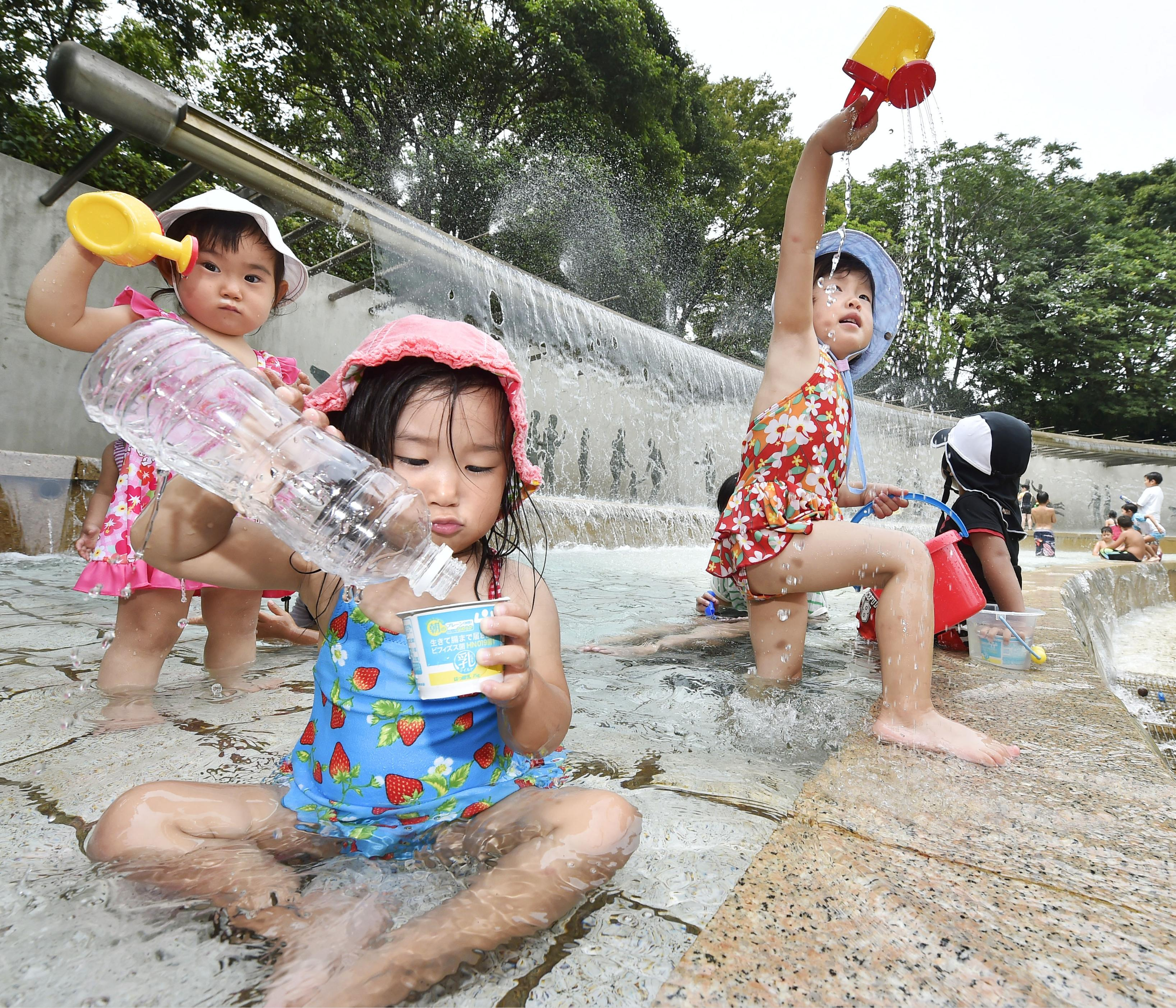Children play with water in a fountain in Edogawa Ward, Tokyo, on Wednesday. Mercury hit the highest levels this summer in many areas of the nation.   KYODO