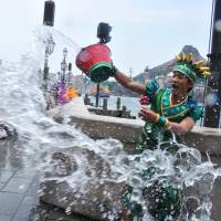 A Tokyo DisneySea cast member (right) throws water toward guests during a special summer attraction called 'Minnie's Tropical Splash' at Tokyo DisneySea in Urayasu, Chiba Prefecture, on Wednesday. | AFP-JIJI