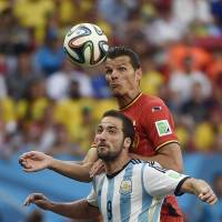 Just a heads up: Argentina's Gonzalo Higuain (left) vies for the ball against Belgium's Daniel Van Buyten during their quarterfinal match at the World Cup on Saturday. | AFP-JIJI