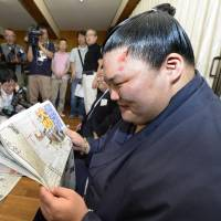 Talk of the town: Goeido reads Monday's newspapers after all but securing promotion to sumo's second-highest rank of ozeki at the Nagoya Grand Sumo Tournament on Sunday. | KYODO