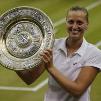 Twice as nice: Petra Kvitova holds the winner's trophy after defeating Eugenie Bouchard in the women's final at Wimbledon on Saturday. Kvitova won the title for the second time. | REUTERS