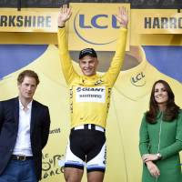 King of the hill: Marcel Kittel celebrates in the overall leader's yellow jersey as Britain's Prince William (right) Catherine, Duchess of Cambridge (second right), and Prince Harry (left), watch after the first stage of the Tour de France, which ended in Harrogate, England. | AFP-JIJI