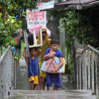 Residents carry their belongings as they evacuate from their homes in the city of Legazpi, southeast of Manila, on Tuesday as authorities warned of approaching Typhoon Rammasun. Thousands of people fled their homes and ships sheltered from heavy seas in the Philippines as the first major storm of the rainy season strengthened into a typhoon. | AFP-JIJI